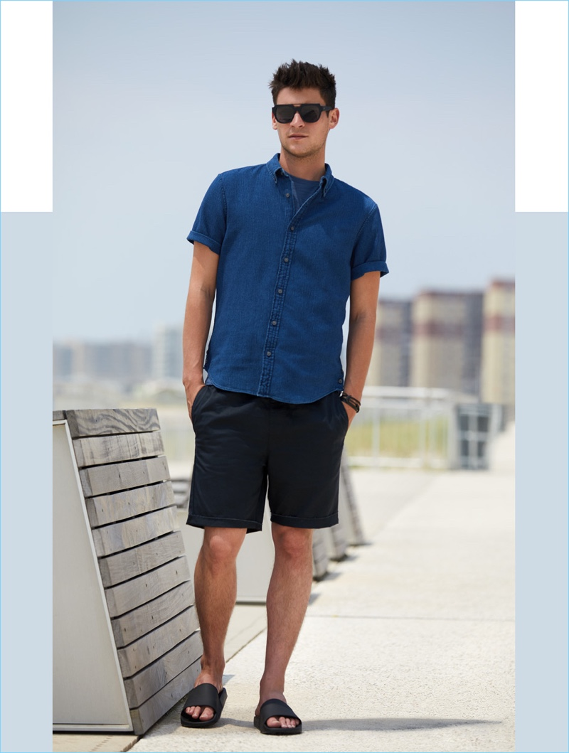 Standing by the smart button-down shirt, Miles Garber wears a short-sleeve shirt $98.50 by Club Monaco. He also dons a Vince tee $65, RVCA shorts $45, a Miansai bracelet $68, and Vince slide sandals $95.