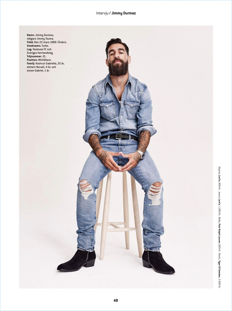 Sitting for a portrait, Jimmy Durmaz wears a denim shirt and jeans by Levi's. He also sports a POLO Ralph Lauren belt and Tiger of Sweden boots.
