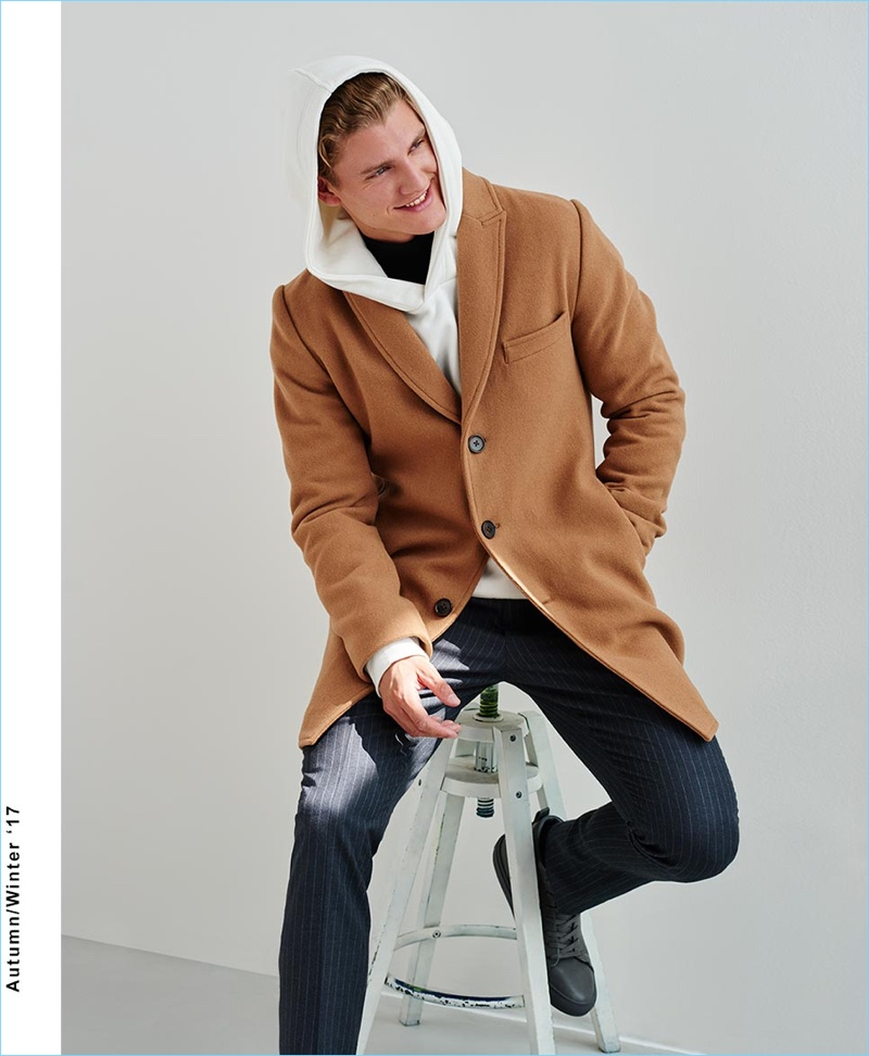 All smiles, Mikkel Jensen wears a camel single-breasted coat with pinstripe pants and a hoodie by Reserved.
