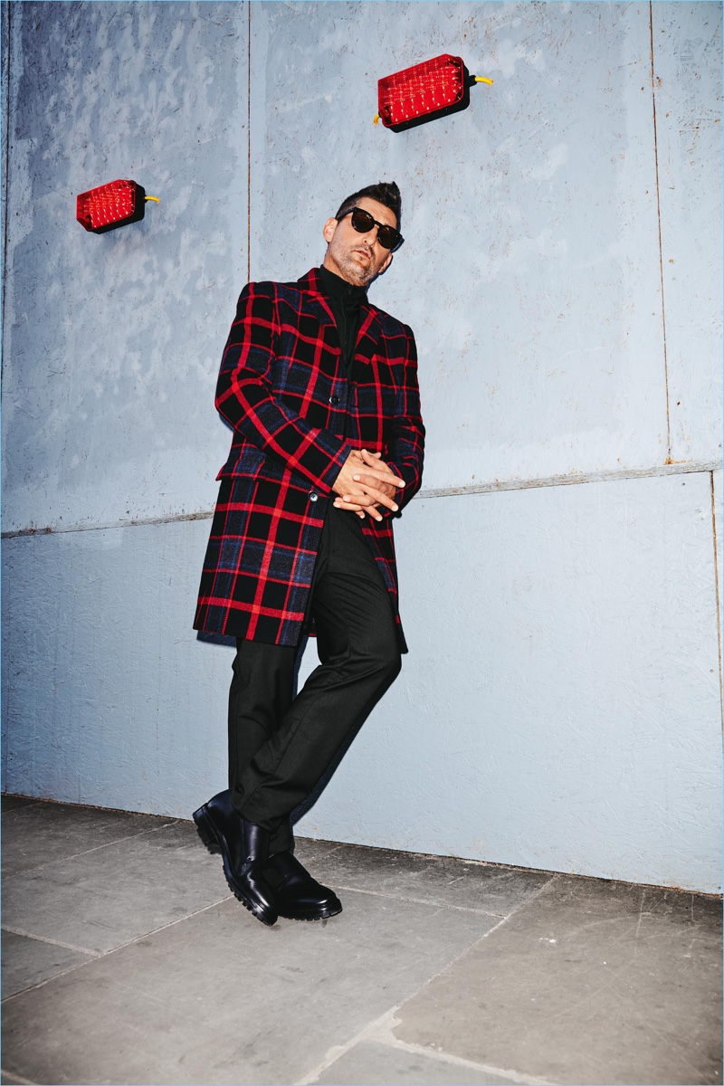 Making a graphic statement, Tony Ward wears a check coat by HUGO. The top model also sports Wormland pants and a half-zip HUGO pullover.
