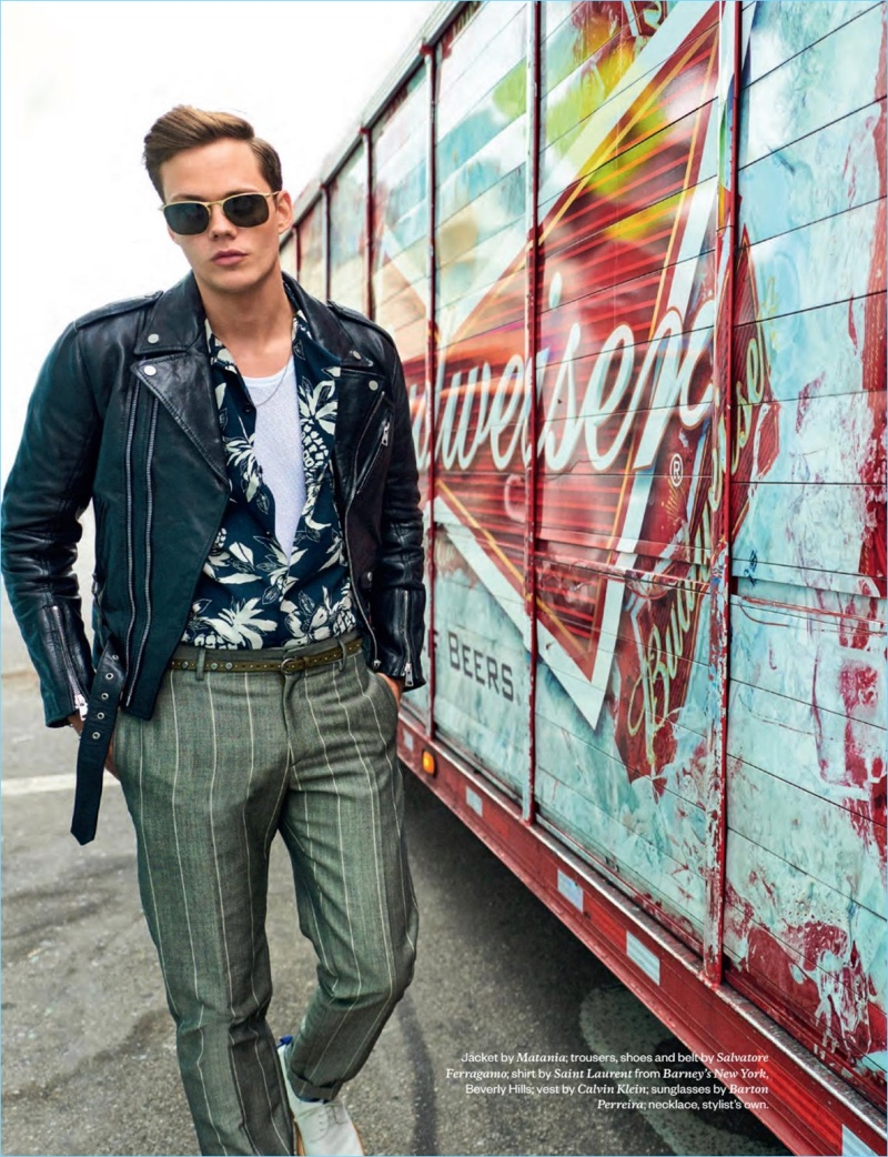 A cool vision, Bill Skarsgård wears a Matania leather biker jacket with a Saint Laurent shirt. Skarsgård also sports a Calvin Klein tank and Barton Perreira sunglasses with trousers and accessories by Salvatore Ferragamo.