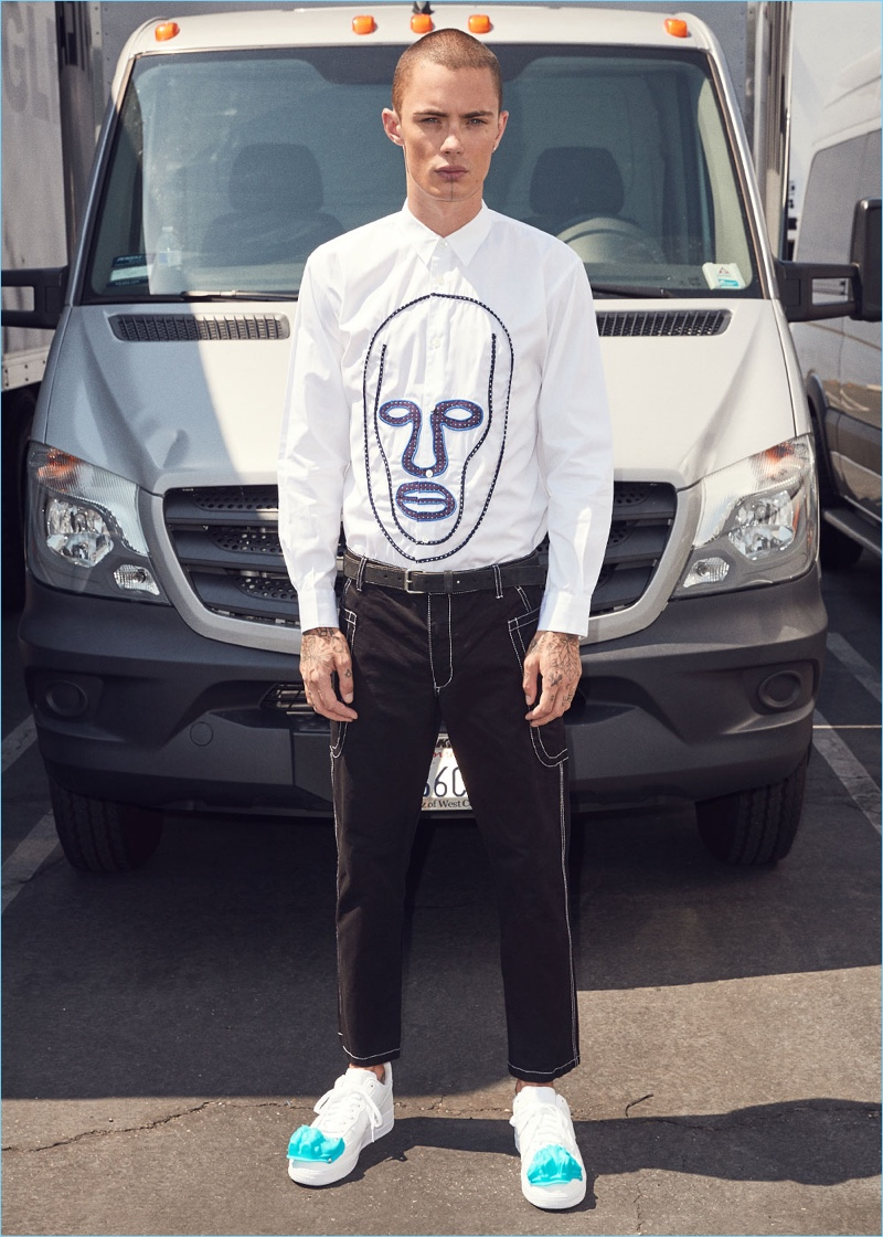 Embracing a black and white look, Simon Kotyk wears a Comme des Garçons Shirt cotton poplin shirt $487 with drill pants $528. Simon's look is complete with Comme des Garçons Homme Plus sneakers $374.