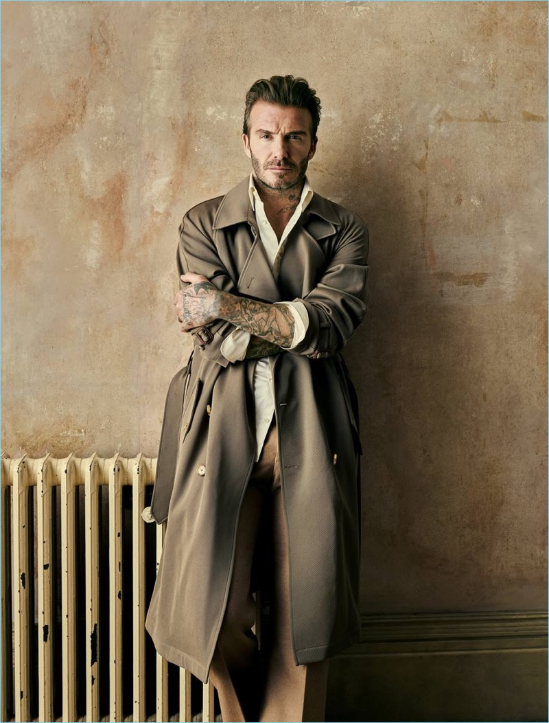 Crossing his arms, David Beckham wears a Ralph Lauren Purple Label silk trench coat with an Alexander McQueen shirt and trousers.