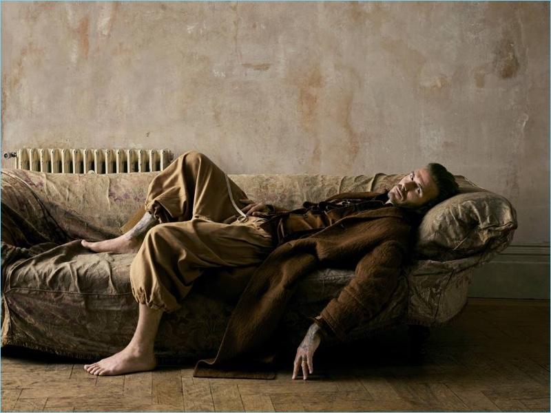 Relaxing, David Beckham wears a Joseph coat with an Etro silk velvet blazer, Kolor shirt, and Vivienne Westwood pants.