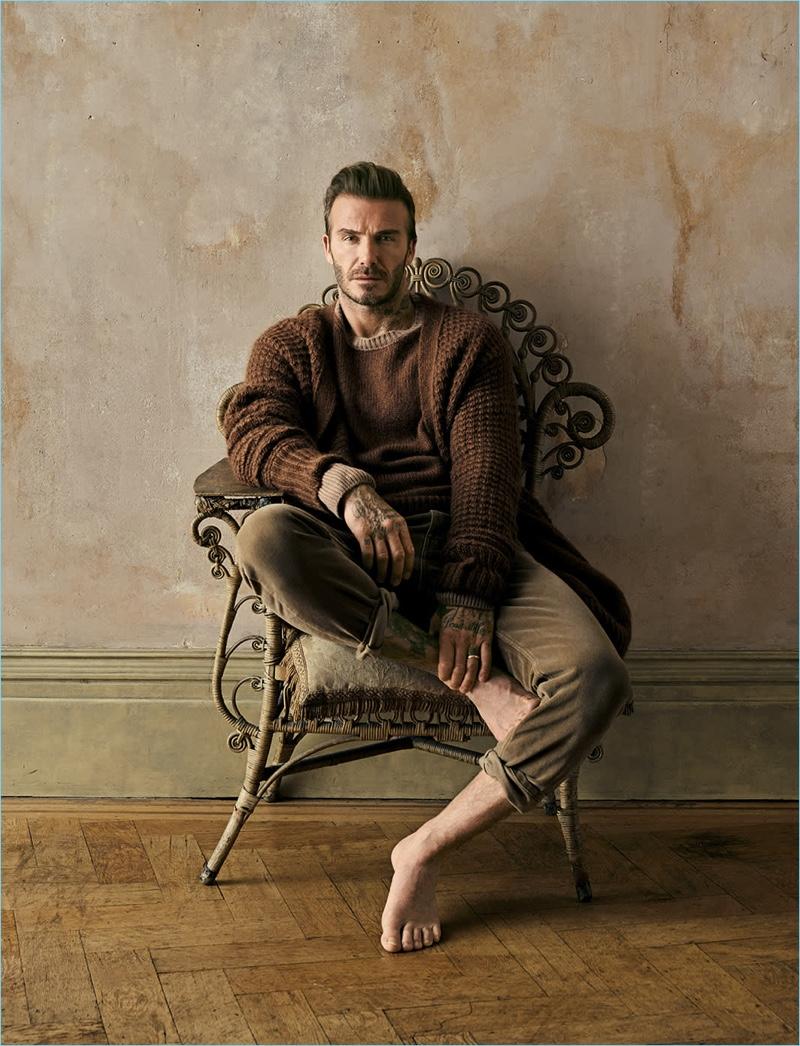 David Beckham sports a brown cardigan, sweater, and pants by Stella McCartney.
