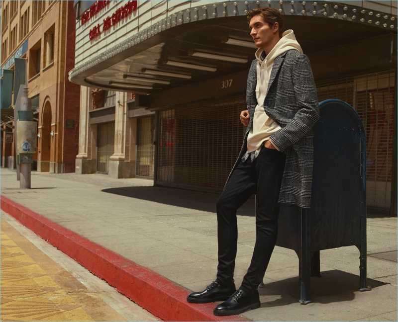 Layering for fall, Matvey Lykov wears a check coat with a hoodie for H&M's fall 2017 campaign.