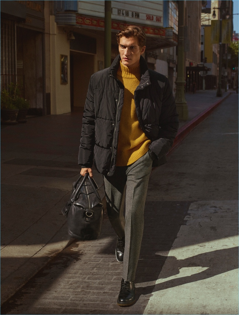 Embracing a pop of color, Matvey Lykov wears a mustard yellow sweater with a quilted jacket and pleated trousers by H&M.