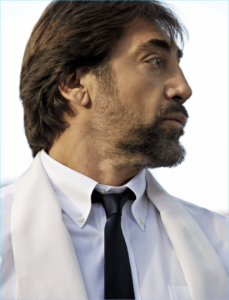 Appearing in a L'Uomo Vogue photo shoot, Javier Bardem wears a Brooks Brother shirt with a Prada tie and Emma Willis scarf.