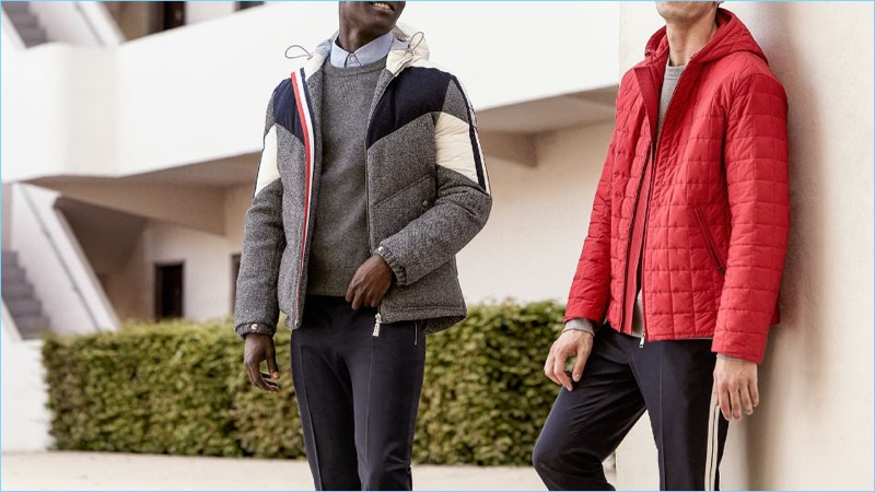 Stay warm and comfortable with these down jackets. Left to Right: Moncler Gamme Bleu hooded down jacket, Thom Browne sweater, Officine Generale oxford shirt, and Valentino trousers. Prada padded zip-up nylon jacket, Acne Studios sweatshirt, and Valentino trousers.