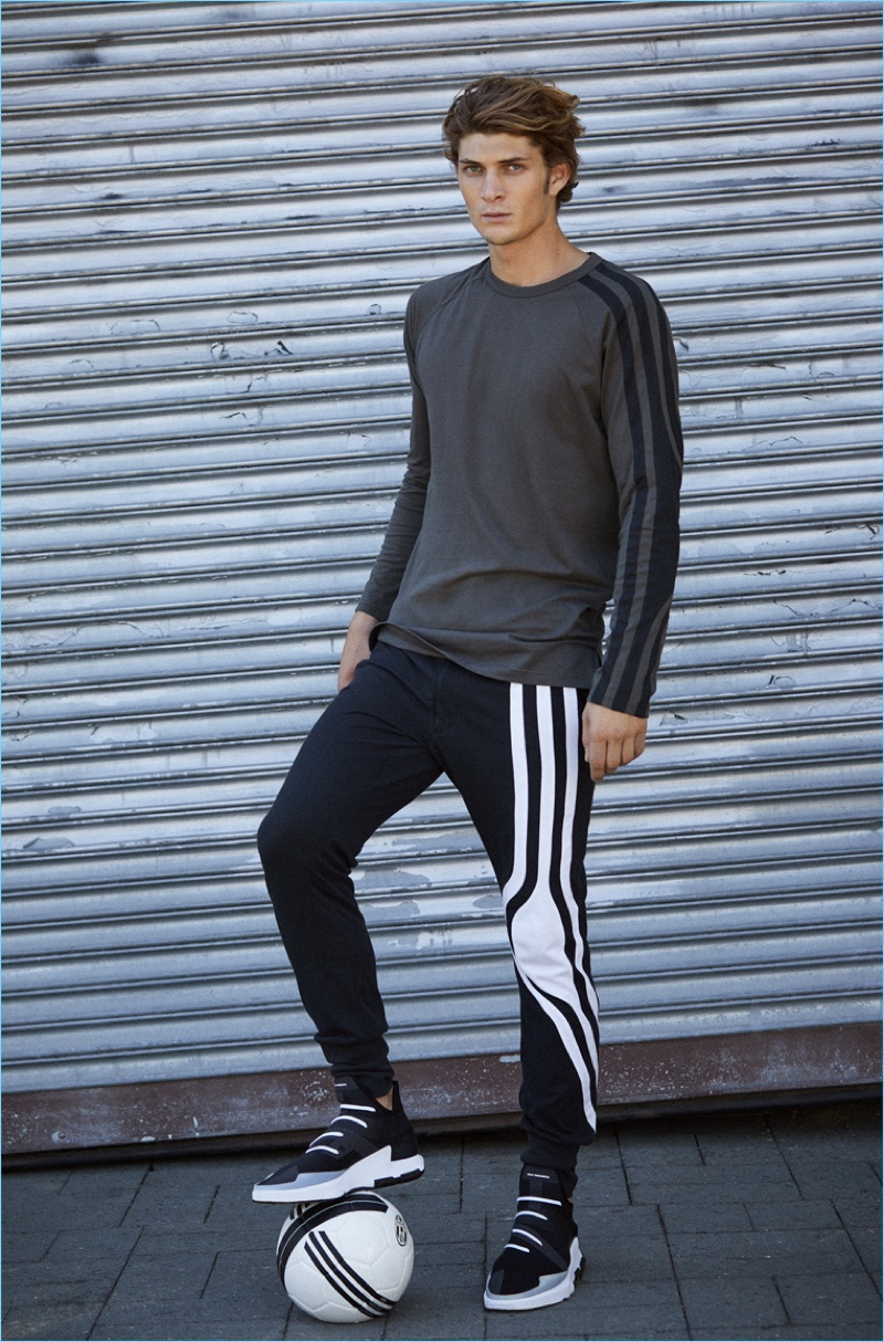 A sporty vision, Jake Lahrman models a Y-3 long-sleeve tee $160, stripes long johns $200, and Noci low sneakers $390.