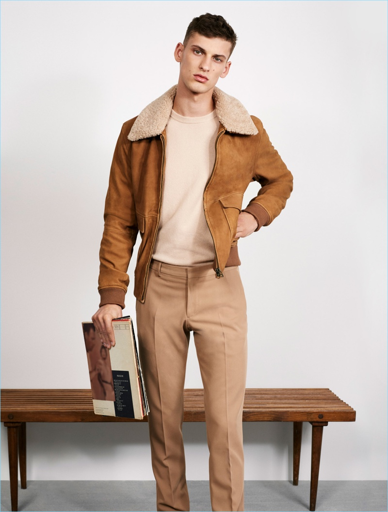 Zara Man makes a case for fall neutrals. Front and center, model David Trulik wears a camel hued aviator jacket with pleated trousers and a crewneck sweater.