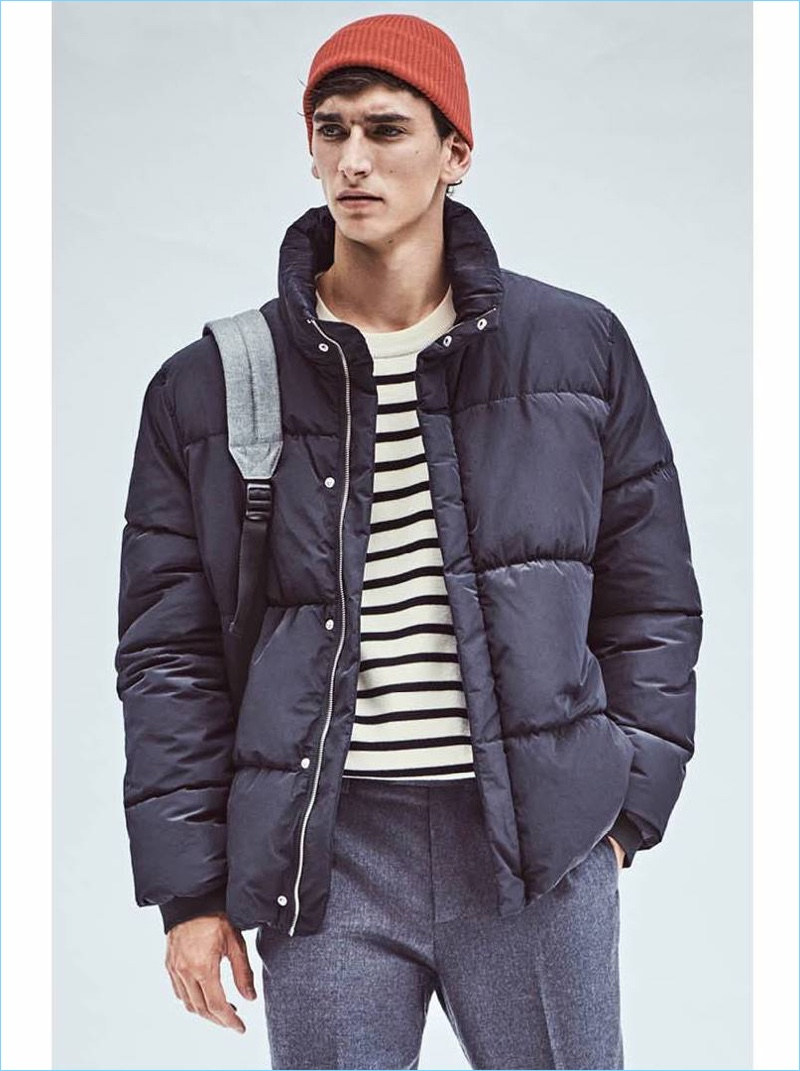 Stepping into casual style, Thibaud Charon wears a H&M padded jacket $79.99 and striped sweater $39.99. He also wears a red knit beanie $9.99 and suit pants $59.99.