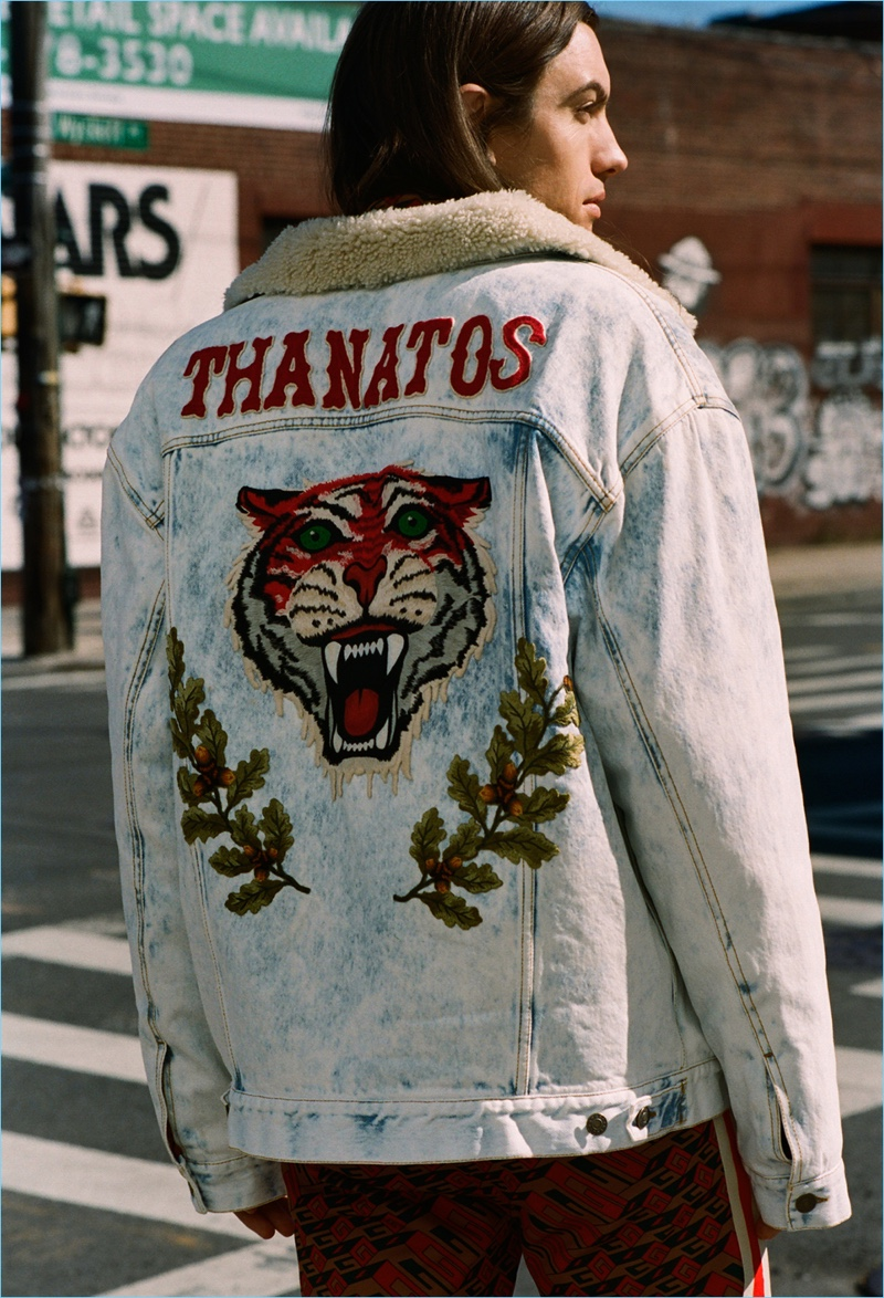 Model and music artist Ian Mellencamp wears a Gucci tiger-embroidered denim jacket with track pants.