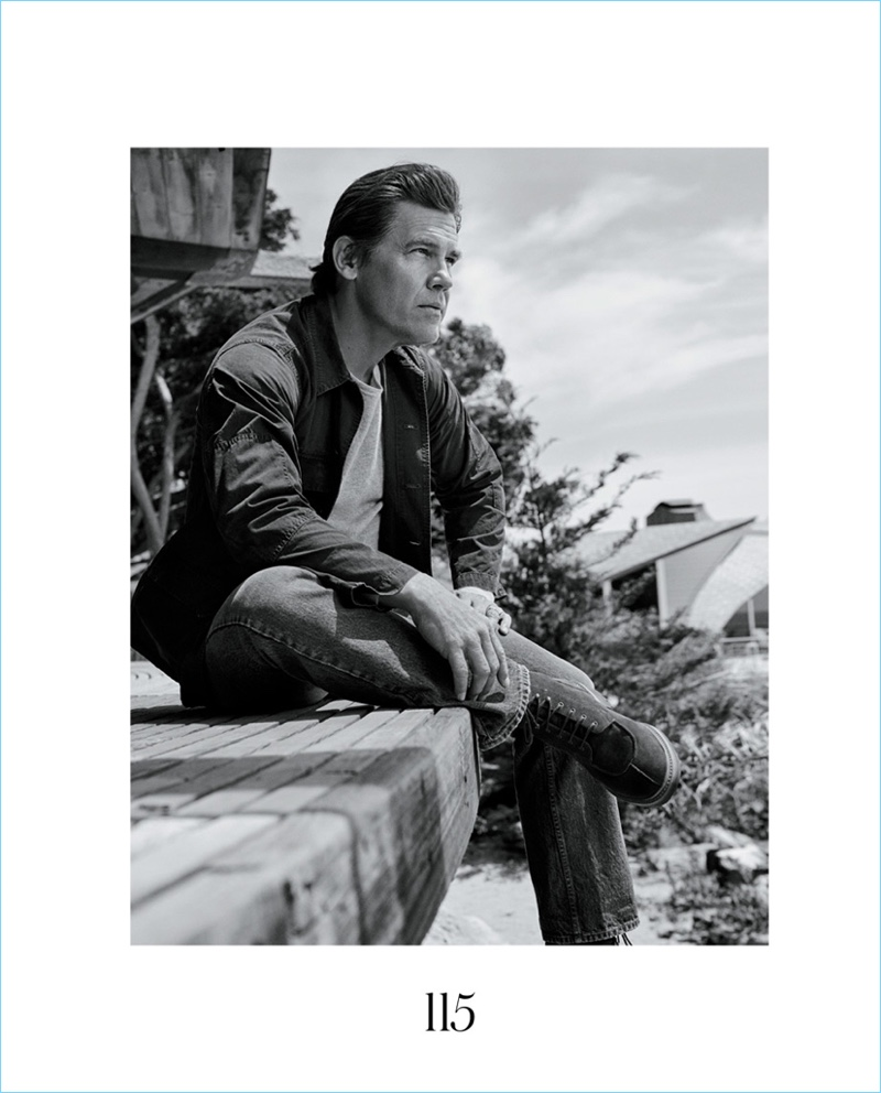 Sitting for a picture, Josh Brolin wears a Blue Blue Japan shirt with a Current/Elliott t-shirt. He also sports Dries Van Noten jeans and Grenson boots.