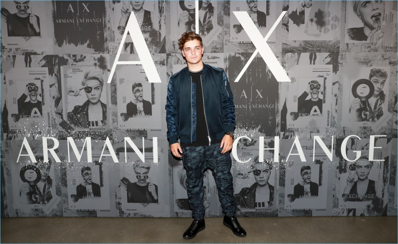 Martin Garrix rocks a sporty look from Armani Exchange. He wears a bomber jacket with camouflage joggers and black sneakers.