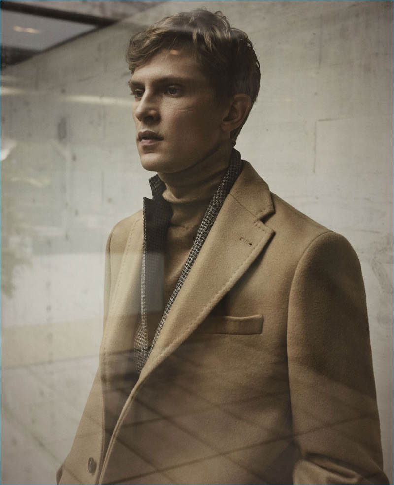 Embracing fall styles, Mathias Lauridsen wears a camel coat with a houndstooth blazer and turtleneck by Massimo Dutti.