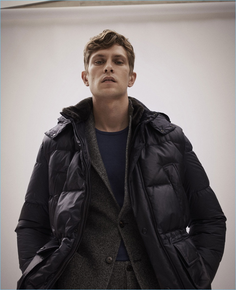 Layering for winter, Mathias Lauridsen wears a down jacket, herringbone suit, and sweater by Massimo Dutti.