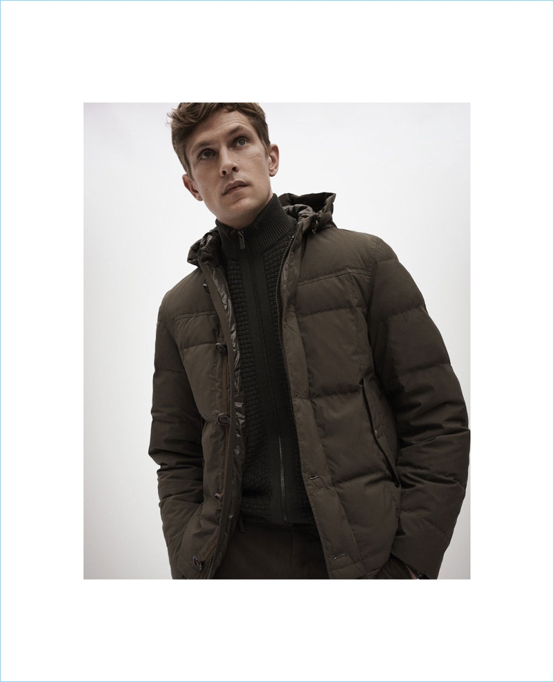 Model Mathias Lauridsen dons a Massimo Dutti down puffer jacket with a textured cardigan sweater.