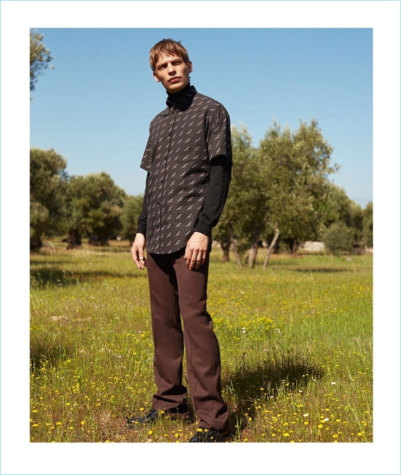 Baptiste Radufe wears a logo print short-sleeve shirt by Balenciaga with a Boglioli sweater. He also sports Valentino trousers and AMI shoes.