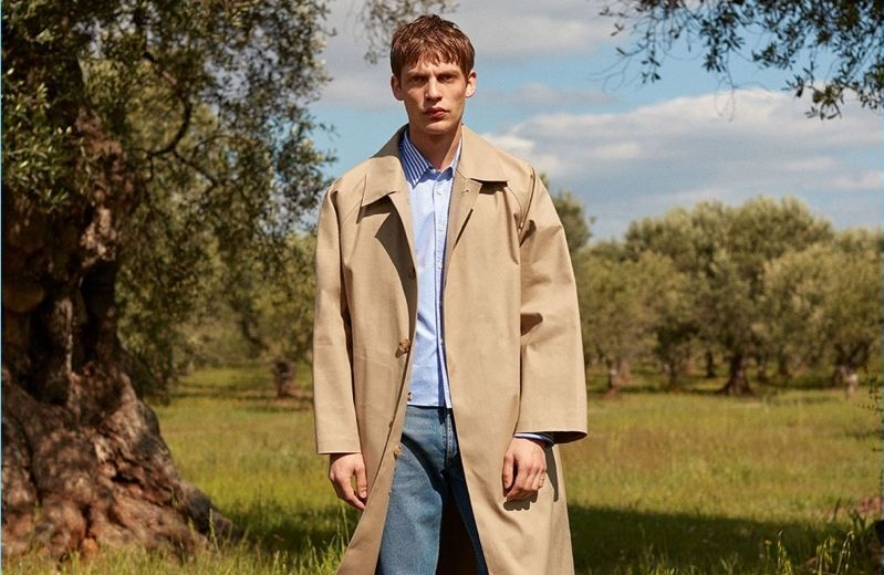 French model Baptiste Radufe dons a Mackintosh trench coat with a striped Commes des Garçons Shirt striped shirt. His look is complete with Balenciaga jeans and AMI shoes.