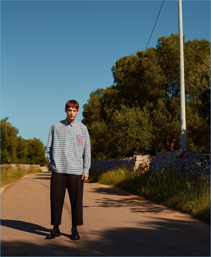 Stepping outside, Baptiste Radufe wears a shirt by Comme des Garçons Shirt with Craig Green trousers and Alexander McQueen shoes.