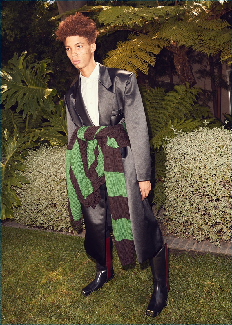 Formal and casual style collide. Tay Godsey models a Raf Simons satin coat and pants. He also wears a Raf Simons shirt and cardigan sweater. Calvin Klein 205W39NYC western boots complete his look.