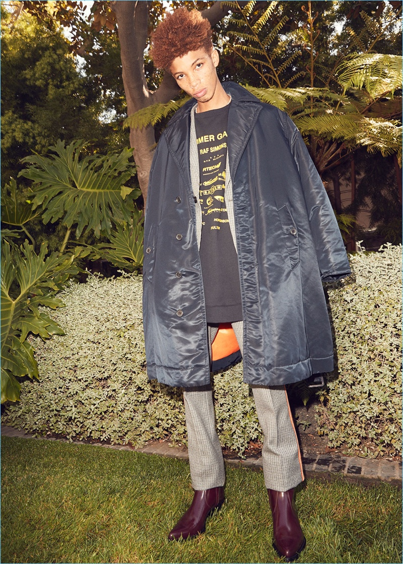 A Calvin Klein 205W39NYC satin jacket represents Raf Simons' modern style. Here, Tay Godsey wears it with a suit and western boots by the brand. Raf Simons' oversize sweatshirt completes Tay's look.