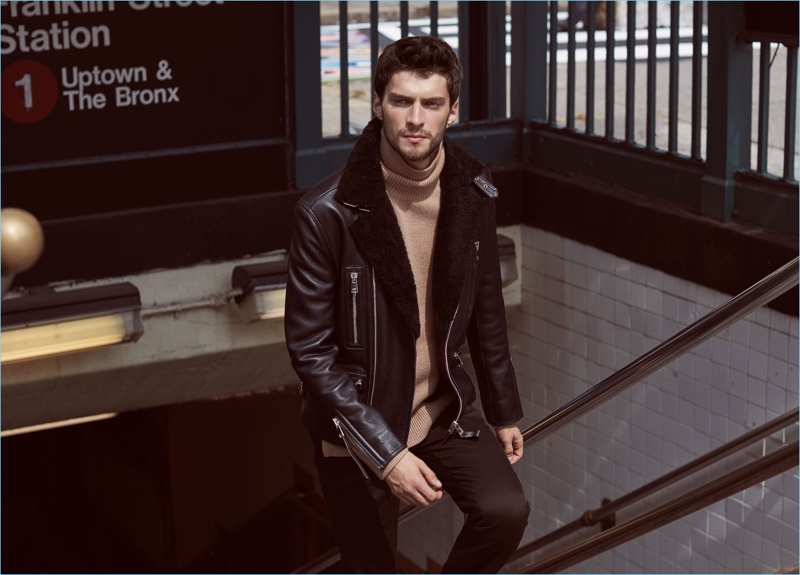 Chic meets cool as Matthew Bell models a Reiss shearling collar biker jacket $1,120. The statement piece pairs well with a camel turtleneck sweater $240 and slim-fit chinos $210.