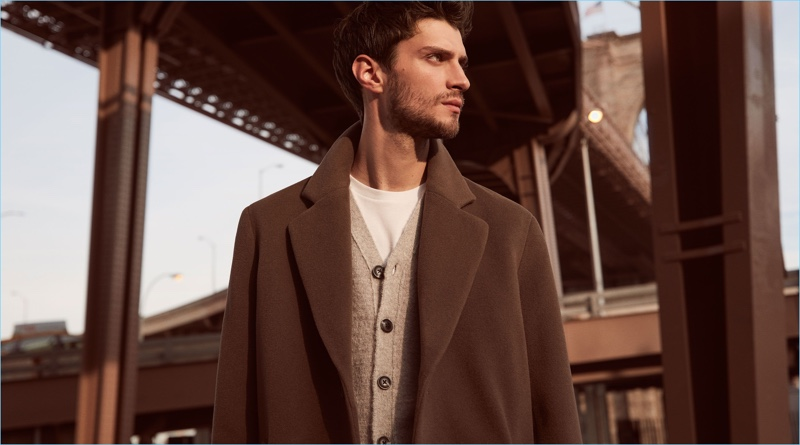 Matthew Bell dons a Reiss cashmere blend overcoat $660 with a cardigan $220 and t-shirt $50.