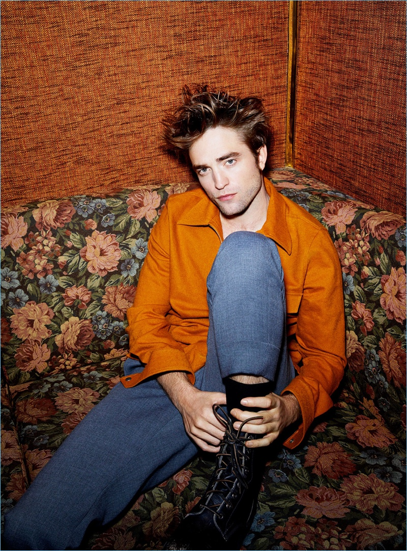 Relaxing, Robert Pattinson wears an AMI blouson jacket and trousers by AMI. He also sports Frye leather boots.