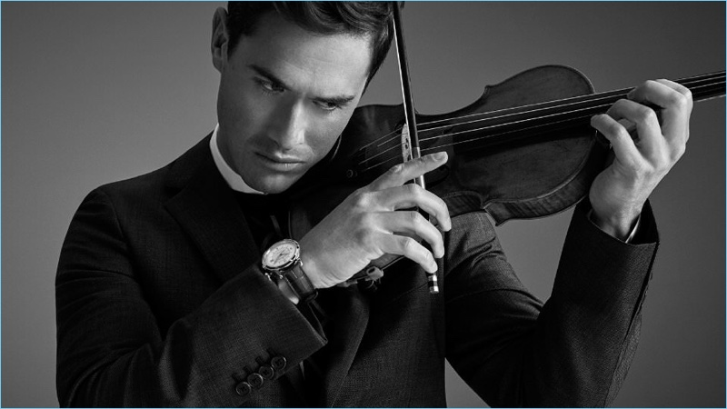 Playing the violin, Charlie Siem wears a Prada wool suit and sweater. He also sports a Jil Sander shirt and Jaeger-LeCoultre watch.