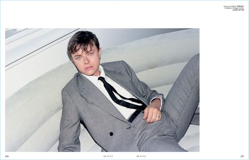 Relaxing, Dane DeHaan wears a Versace suit.