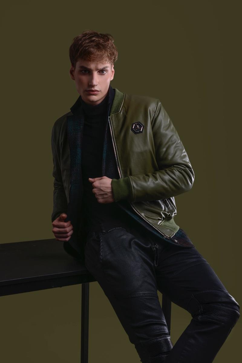 Felix Velbinger wears check jacket Daks, pants and green leather jacket Philipp Plein.