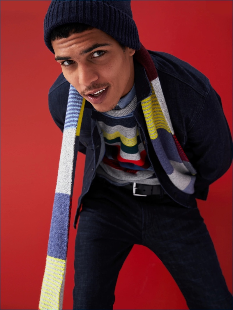 Gap proposes colorful stripes. Here, Geron McKinley models a stripe sweater with a chambray shirt. He also wears a striped scarf, denim jacket, and skinny-fit jeans.