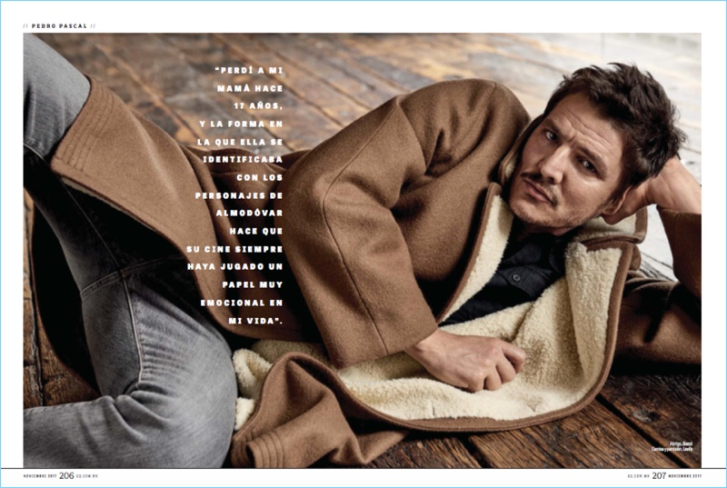 Laying down, Pedro Pascal wears a Gucci coat with a shirt and pants by Levi's.