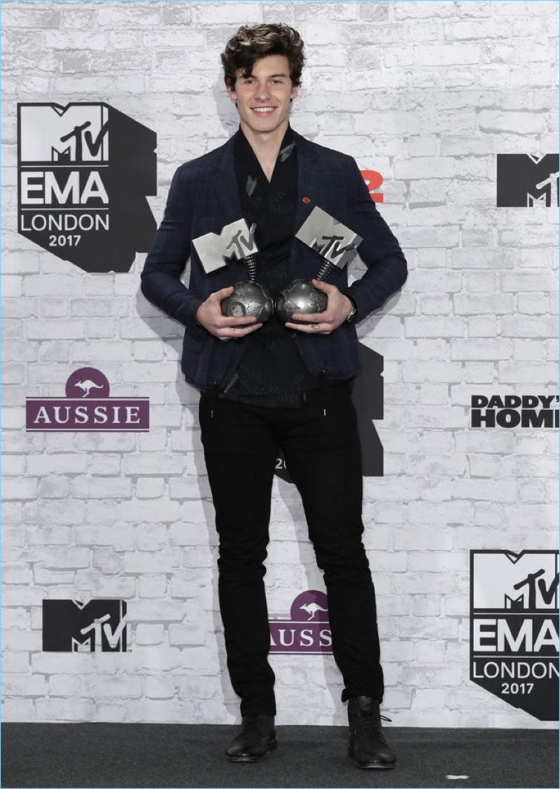 Shawn Mendes wears an Emporio Armani midnight blue blazer and black kimono evening shirt. He also dons the label's black trousers and sneakers.