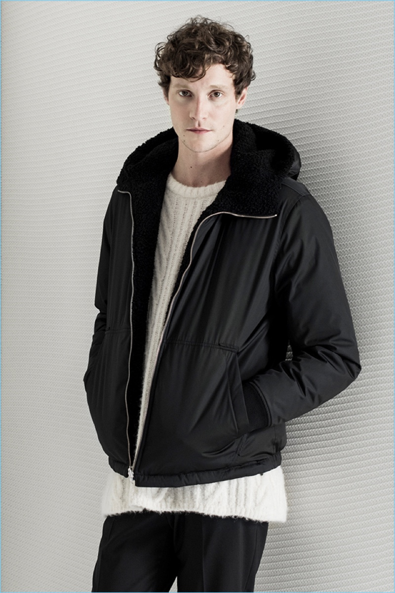 Matthew Hit sports a Theory cable-knit sweater and sherpa-lined jacket. He also wears Theory's stretch wool pants.