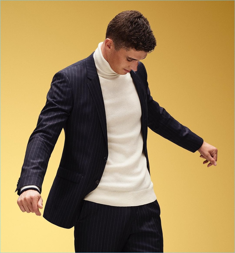 English model Matthew Holt sports a chic turtleneck and suit by Tommy Hilfiger.