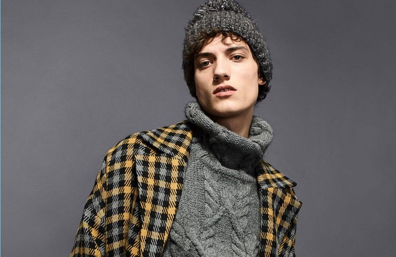 Serge Rigvava wears a Zara Man oversized cable-knit turtleneck with a check winter coat.