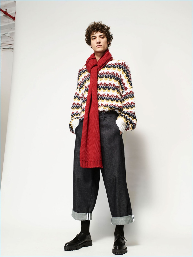 Making a seasonal play, Serge Rigvava models a Zara Man jacquard knit with a red scarf and smart trousers.