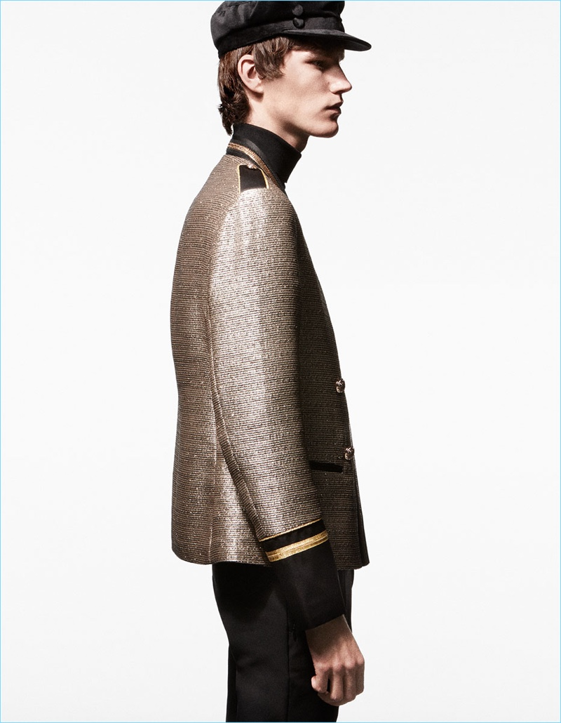 Delivering a side profile, Elias de Poot wears a gold military-style jacket by Zara Man.