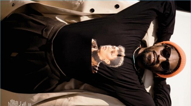 Appearing in a shoot for GQ Style, André 3000 Benjmain wears a BOSS coat and pants with a custom t-shirt.