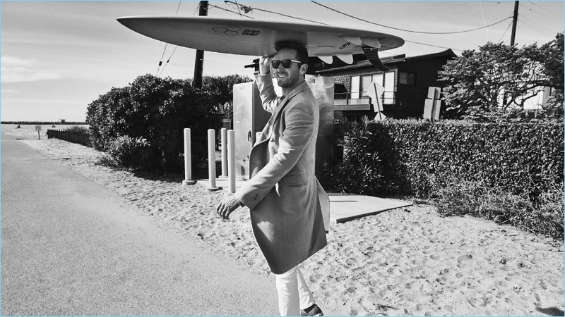 Taking to the beach, Armie Hammer wears a Calvin Klein coat, Schiesser sweatshirt, and Acne Studios jeans.