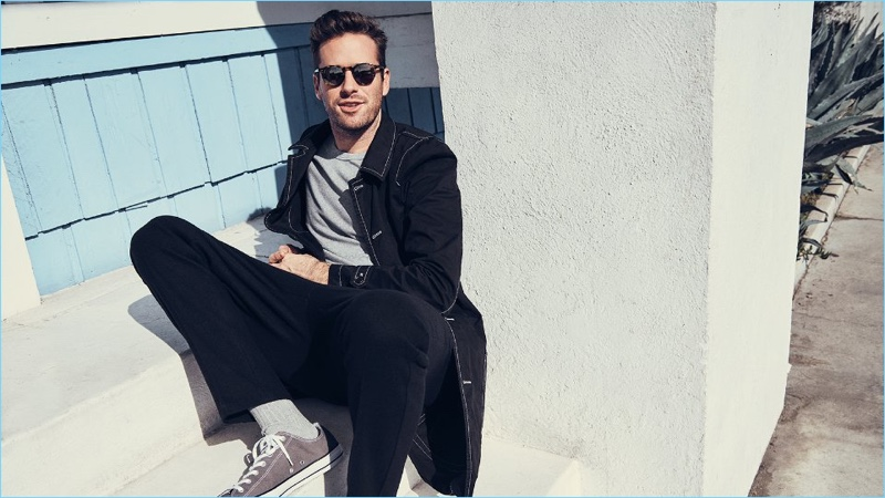 Relaxing, Armie Hammer wears a Comme des Garçons SHIRT jacket, Schiesser t-shirt, AMI trousers, Oliver Peoples sunglasses, and Converse sneakers.