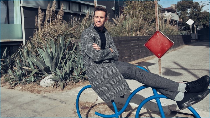 Connecting with Mr Porter, Armie Hammer wears a Solid Homme coat and Tom Ford polo shirt. He also sports NN07 trousers and Converse sneakers.