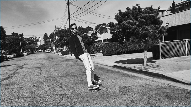 Skateboarding, Armie Hammer wears a Kent & Curwen corduroy bomber jacket. Hammer wears a Maison Margiela t-shirt, Acne Studios jeans, and Converse sneakers as well.
