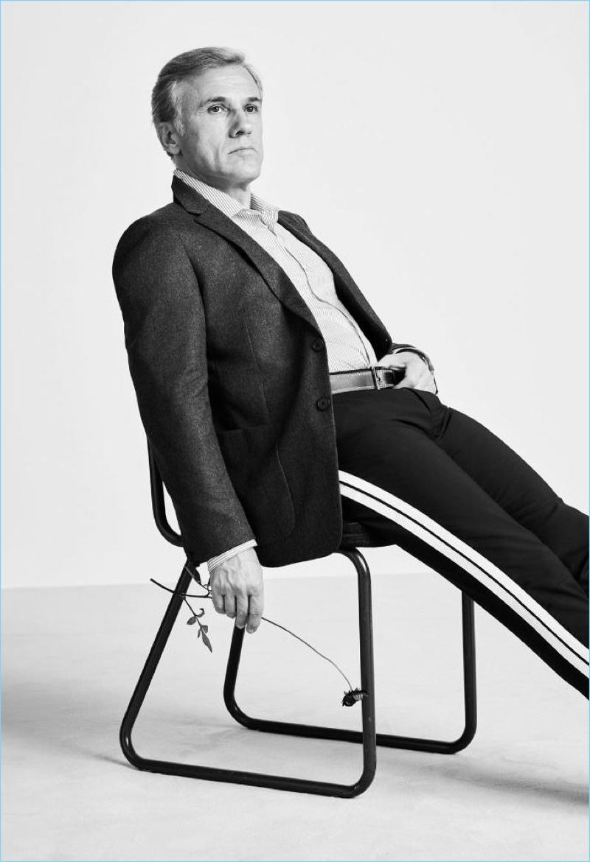 Sitting for a photo, Christoph Waltz sports a Prada blazer, Joseph shirt, Valentino trousers, and Loewe belt.