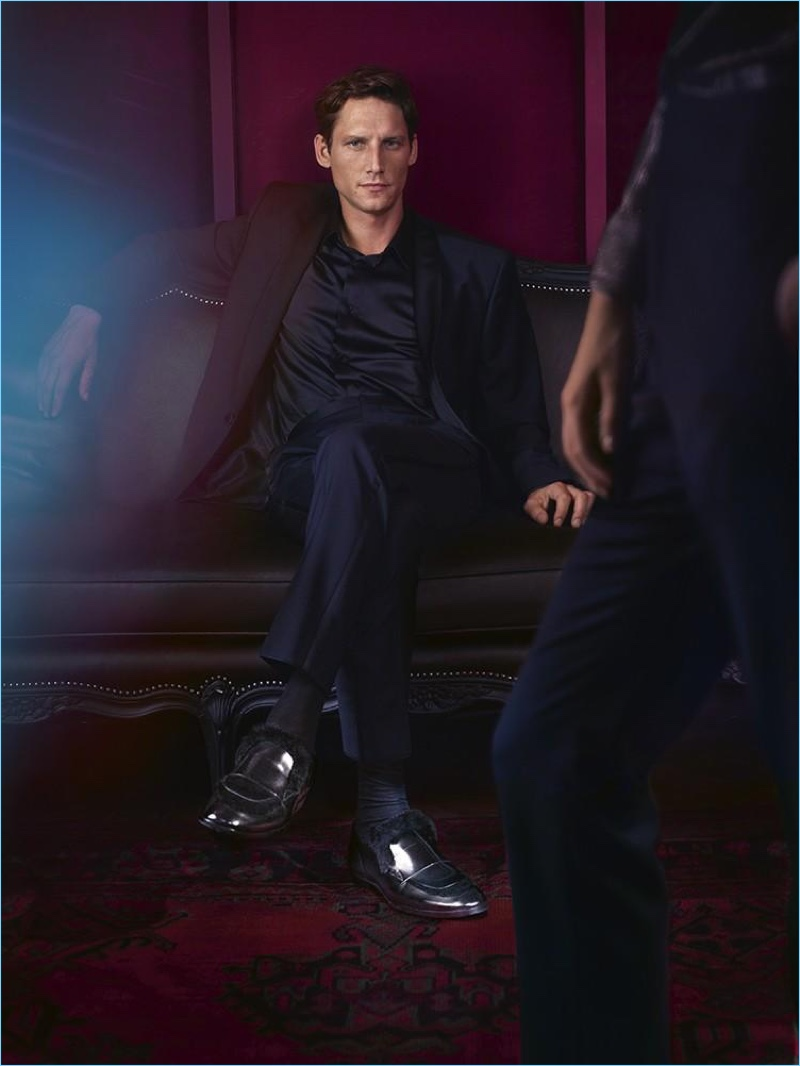 Model Roch Barbot wears Jimmy Choo black brushed off leather loafers with rabbit fur.