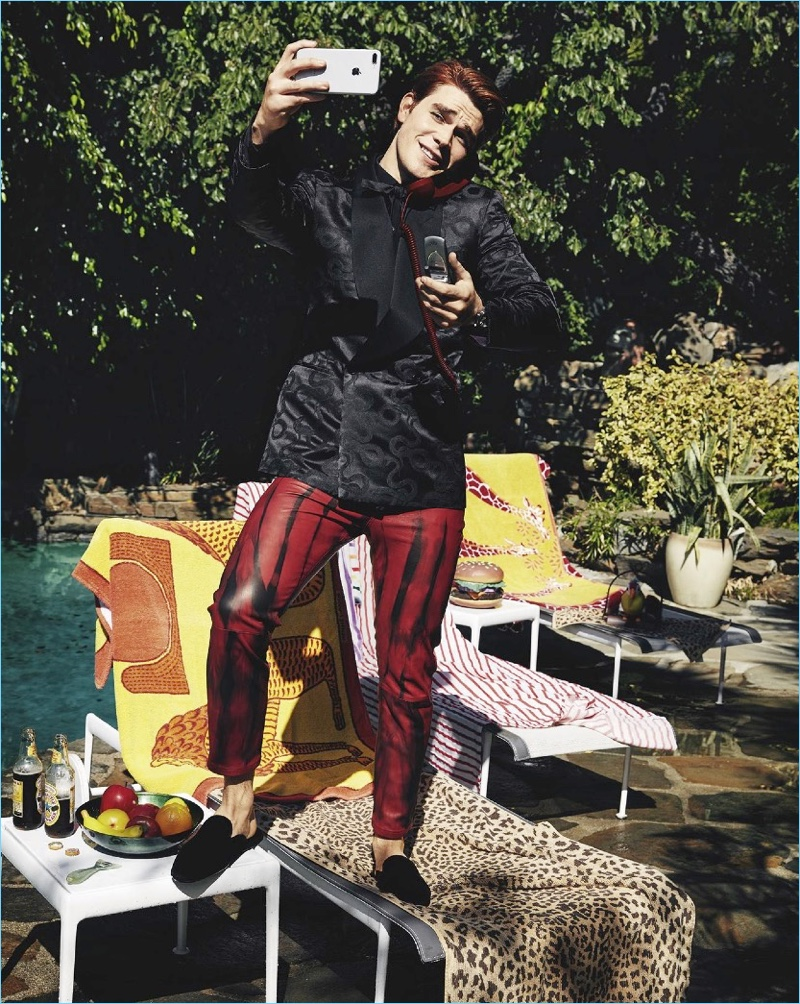 Posing for a selfie, KJ Apa sports a shirt, jacket, and bow-tie by Ralph Lauren Purple Label. He also wears Ann Demeulemeester pants and Dolce & Gabbana shoes.