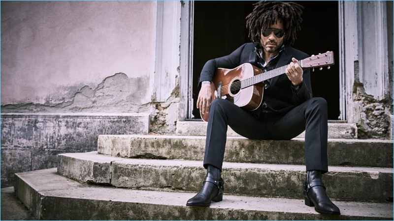 Playing the guitar, Lenny Kravitz wears a Saint Laurent tuxedo and boots with an Alexander McQueen shirt and Gucci sunglasses.